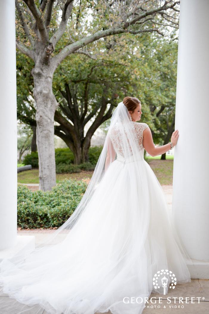 elegant bride leaning on white pillars