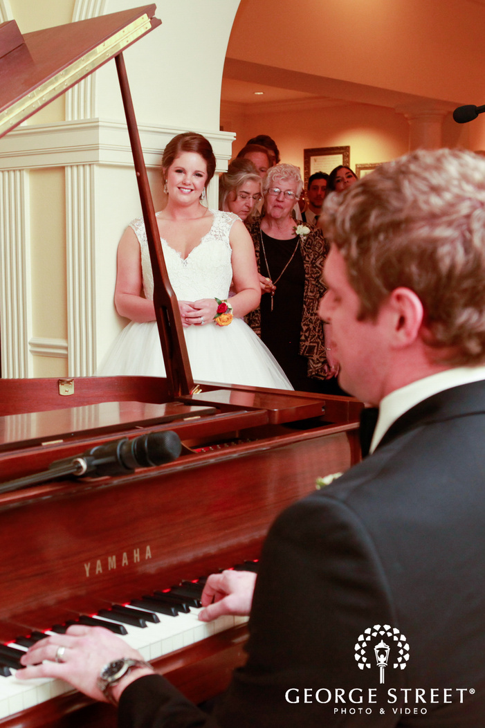 groom playing piano for bride at reception