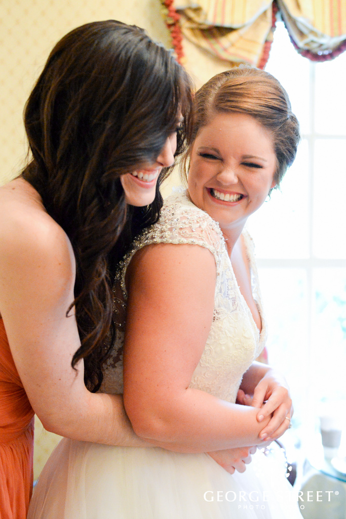 laughing bridesmaid hugging bride