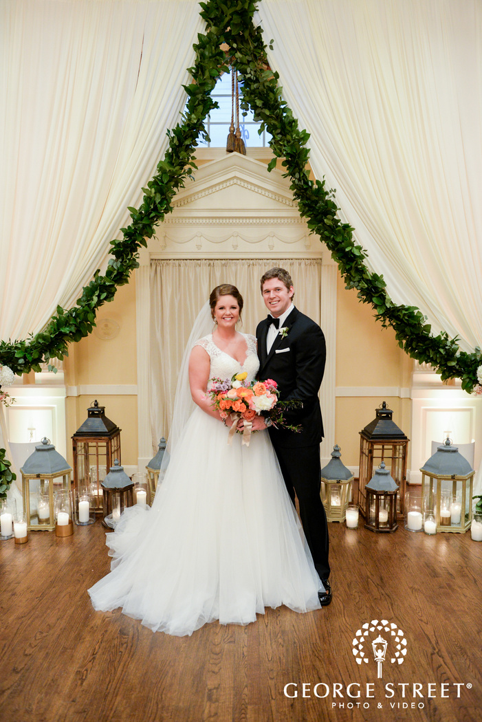 smiling bride and groom with candles and lantern decor