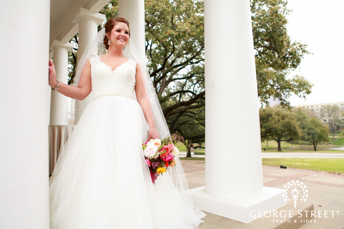 smiling bride leaning on pillar