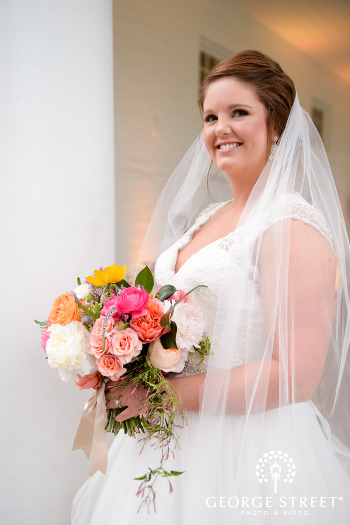smiling bride posing with bouquet