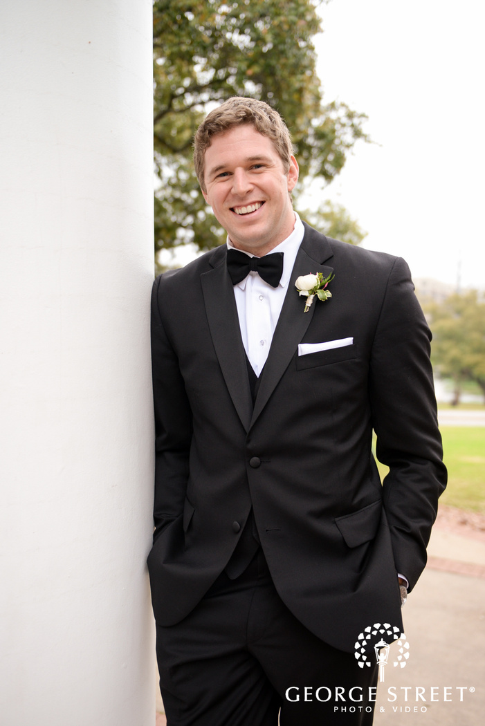 smiling groom leaning on column
