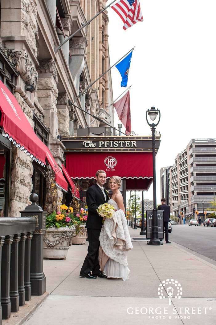 charming bride and groom on a street near hotel entrance at the pfister hotel in milwaukee
