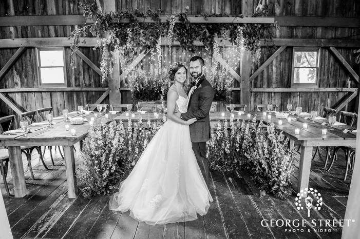 black and white wide shot of newly married couple in front of beautifully decorated wooden dining tables with plants hanging from the ceiling
