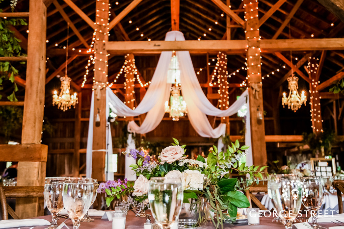 bokeh shot of beautifuly decorated tabletop with glassware candles and multicolor bouquet with draped chandelier in the backdrop