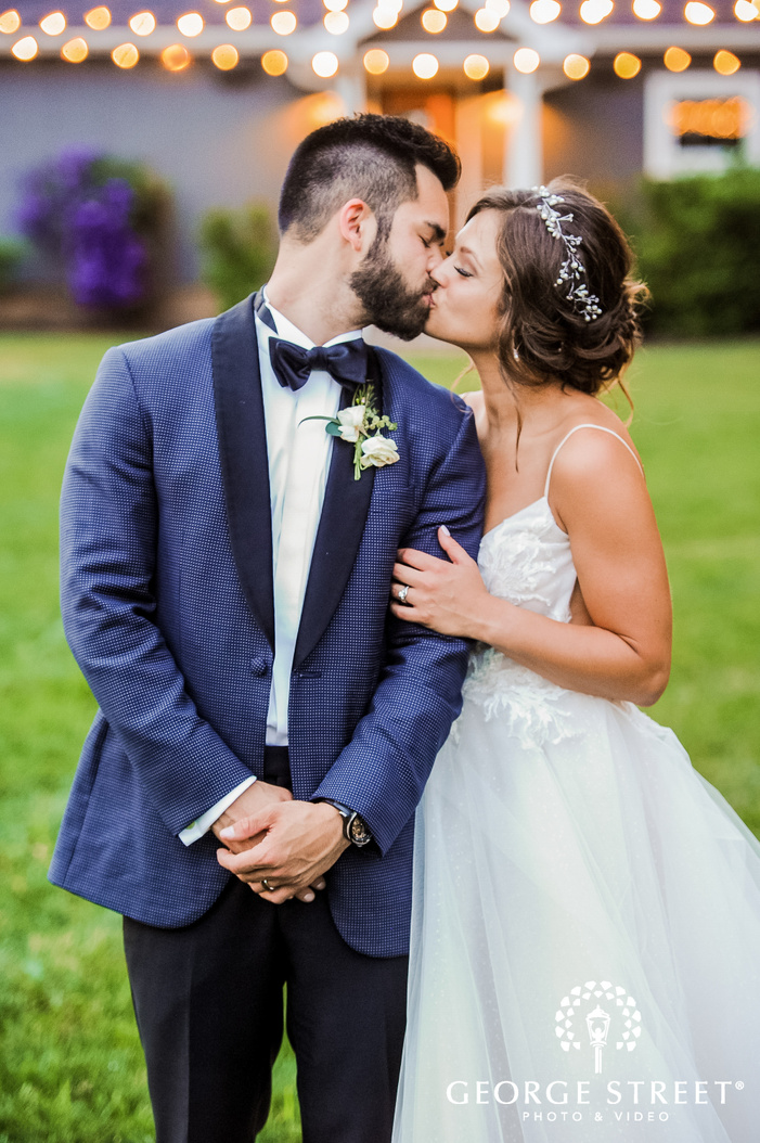 bokeh shot of bride in beautiful wedding outfit kissing the groom dressed in blue suit with fairy lights in the backdrop