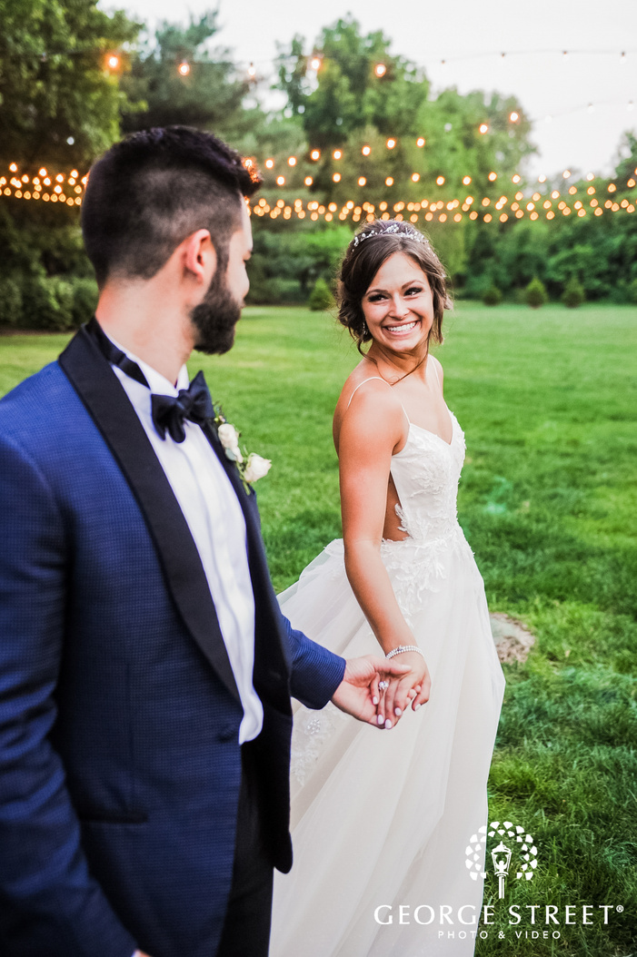 bokeh shot of smiling bride holding the grooms hand in an open lawn with hanging fairy lights in the backdrop