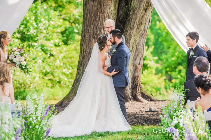 bride and groom kissing after being pronounced married by the officiant at the altar under a tree