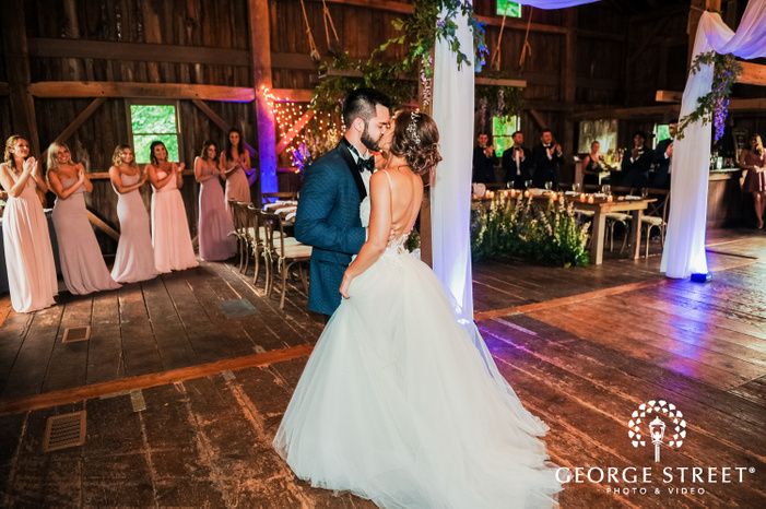 bride and groom kissing in a wooden hall with cheering guests at mustard seed gardens indianapolis