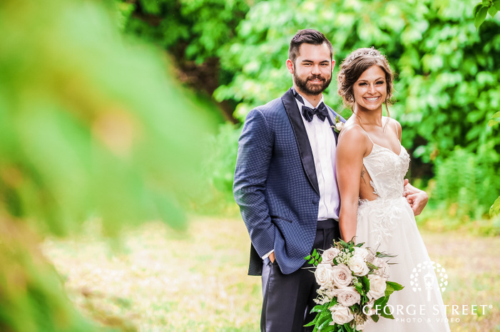 bride in a beautiful laced wedding gown and a white rose bouquet in hand posing along with the groom in classy blue suit