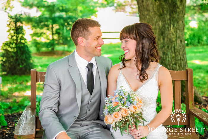 bride with beautiful bouquet in hand sitting alongside the groom on a wooden chair