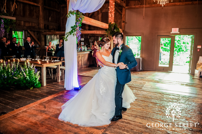 frame showcasing the first dance of a newly married couple in a wooden hall wedding reception