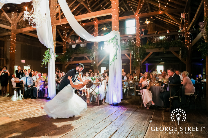 frame showing the first dance of newly married couple in wooden hall under draped crystal chandelier with onlookling guests