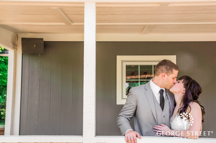 newly married couple kissing with a gray wooden wall in the back wedding photos