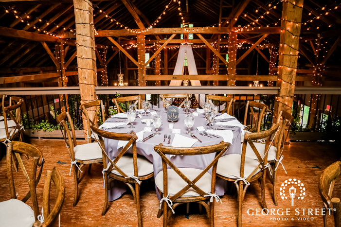 reserved table with cutlery and glassware accompanied by wooden chairs wedding photos