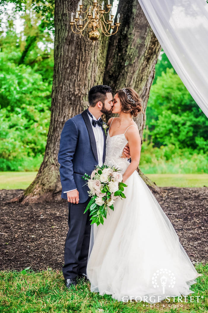 romantic shot of groom kissing the bride  under a golden color chandelier mustard seed gardens indianapolis