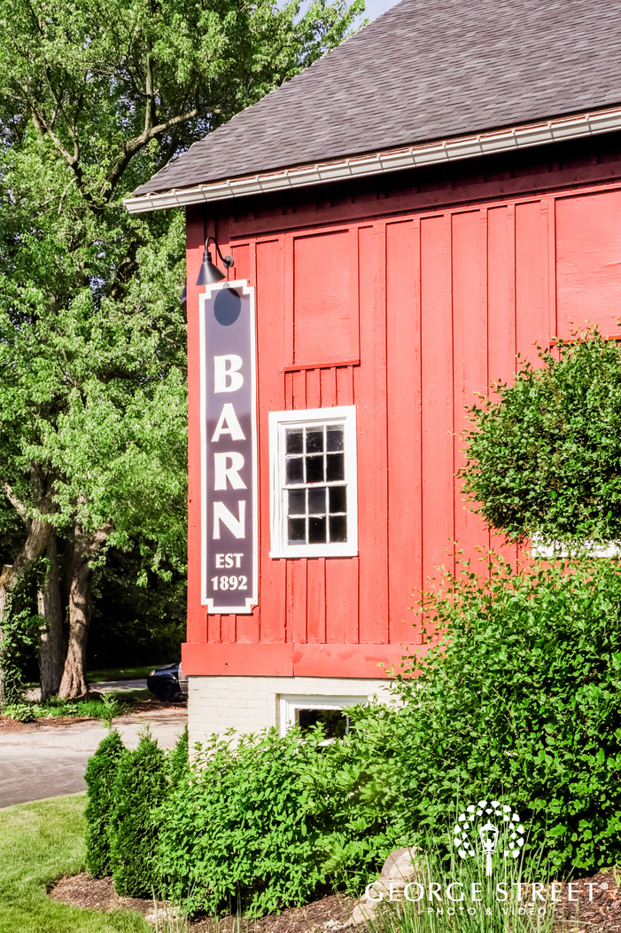 sign outside a red wooden barn that says barn est      with green foliage around wedding venue indianapolis