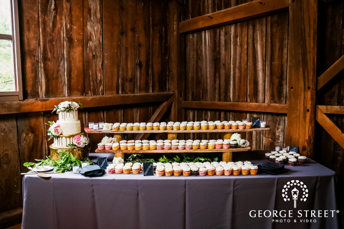 three tiered wedding cake and muffins displayed on wooden counters at mustard seed gardens wedding desserts