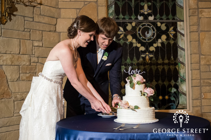 excited bride and groom at cake cutting ceremony
