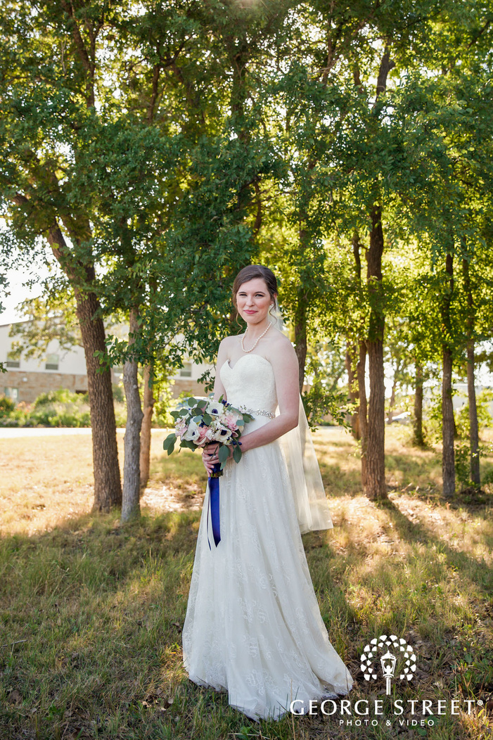 pretty bride with lovely bouquet in yard