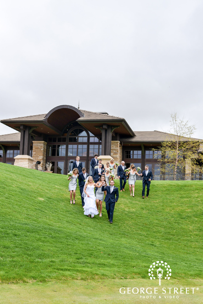 cheerful couple and group walking down the green lawn at sanctuary golf course in denver wedding photo