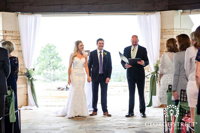 loving couple exit from wedding ceremony at sanctuary golf course in denver wedding photos