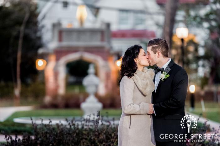 romantic bride and groom near fountain in lawn outside alden castle in boston