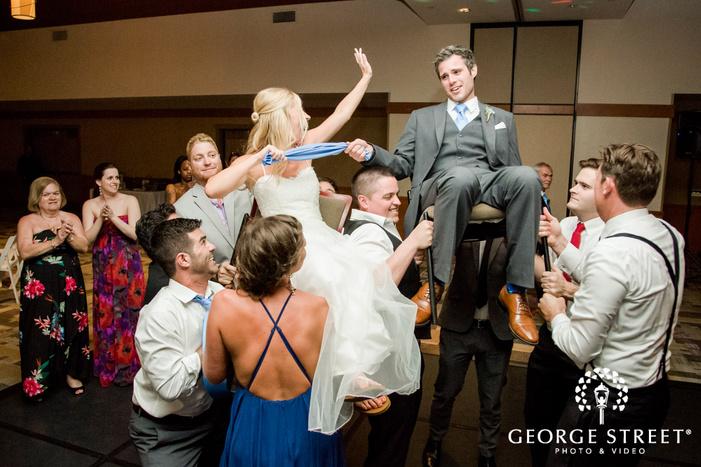 cheerful couple and guests on dance floor coronado community center san diego wedding photos