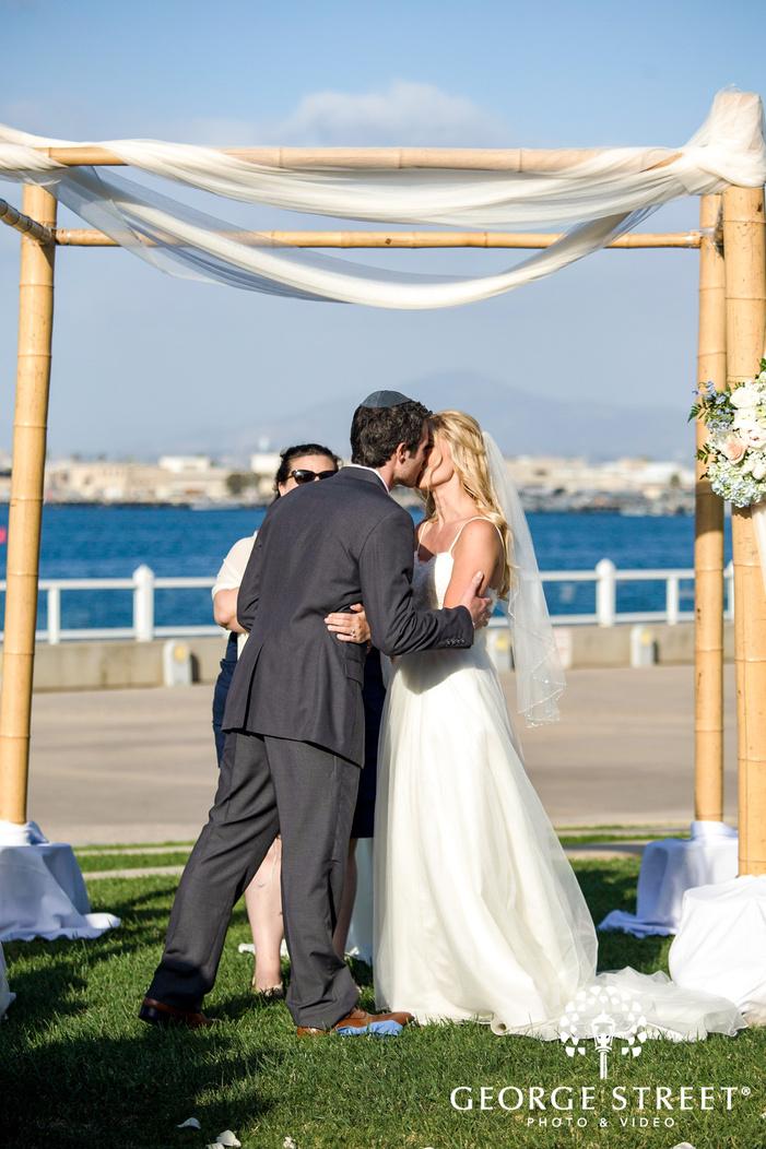 lovely bride and groom first kiss coronado community center san diego wedding photos