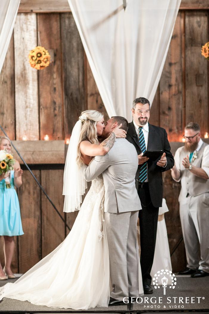 pickering barn seattle wedding ceremony venue bride and groom kiss