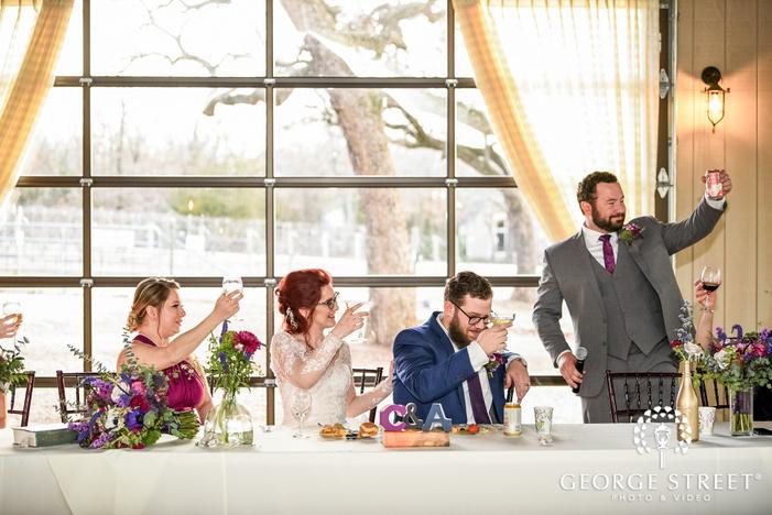 charming couple on reception table during wedding toast wedding photo