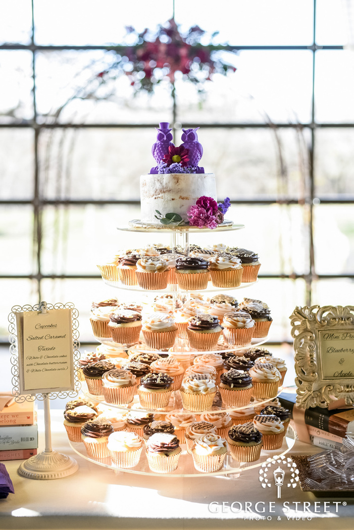 delightful reception cake with topper and cupcakes wedding photo