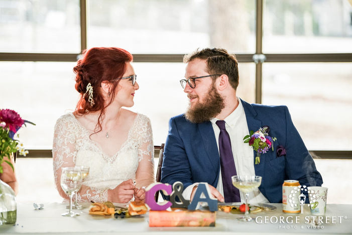 loving bride and groom on reception table wedding photo