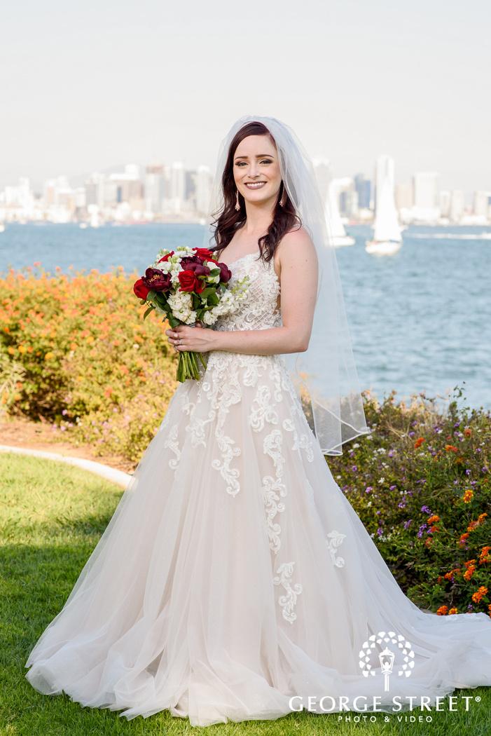 beautiful bride in greenery near seaside wedding photo