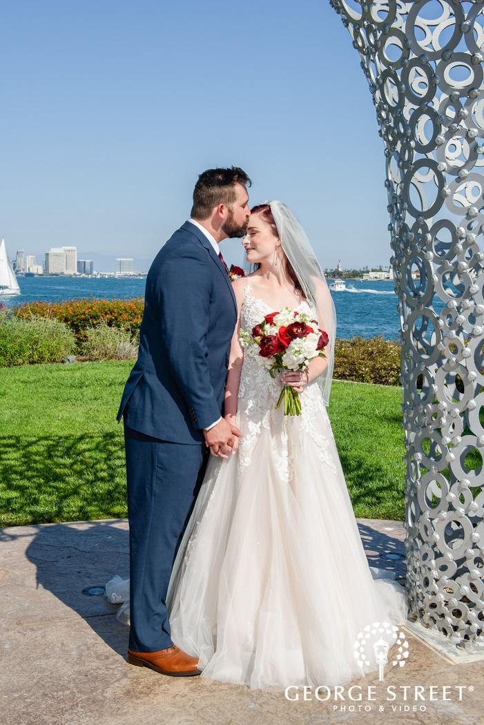 beautiful couple in greenery outside reception venue wedding photo