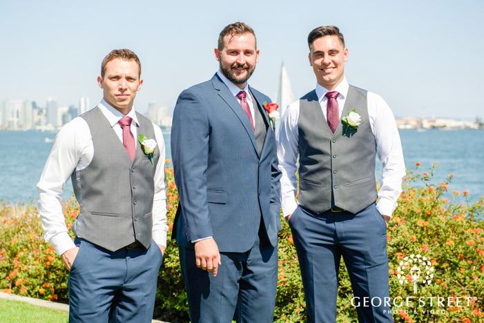 charming groom and groomsmen in greenery outside venue