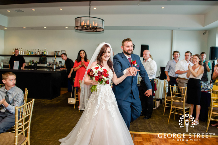 happy couple entering reception venue at tom hams lighthouse in san diego