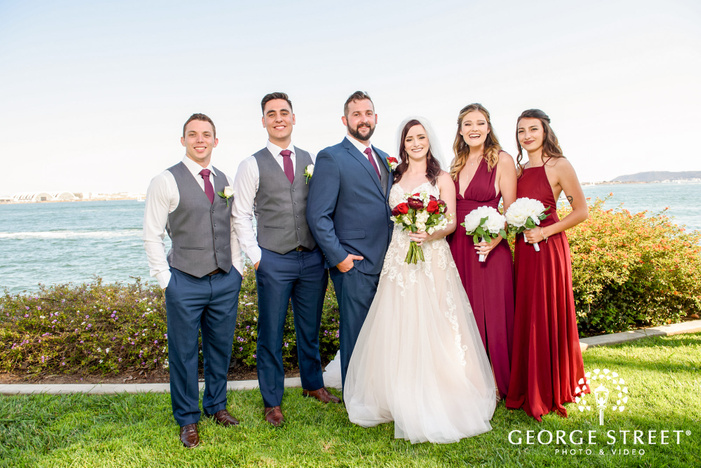 pretty bride and groom with groomsmen and bridesmaids at tom hams lighthouse in san diego