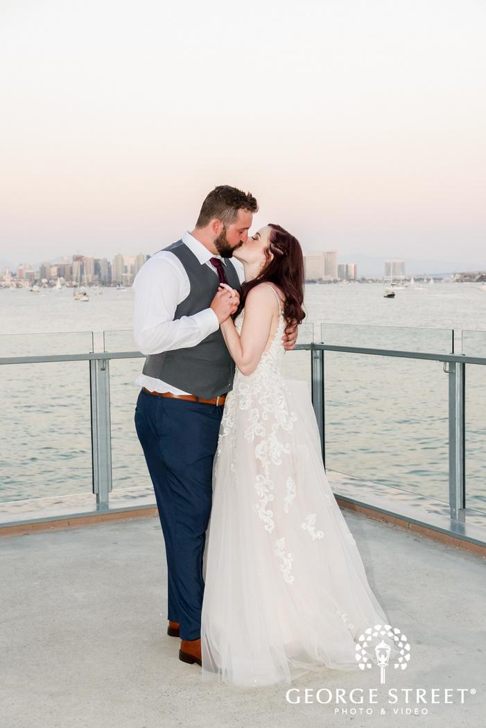 romantic bride and groom kissing near seaside outdoor wedding photo