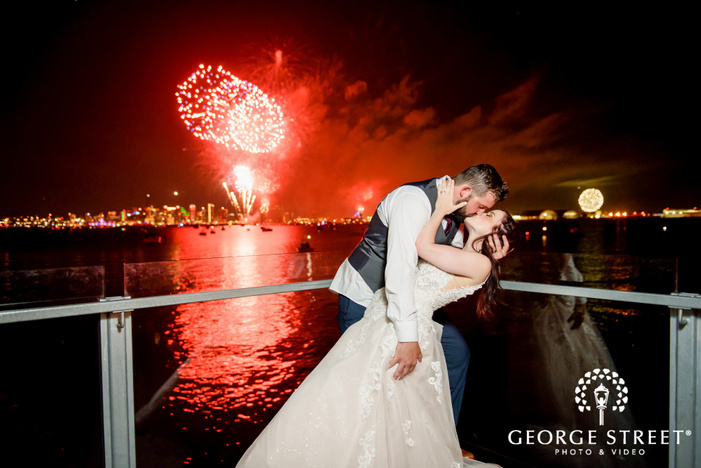 romantic couple kissing under sky fireworks at the back wedding photography