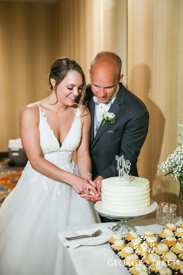 loving bride and groom cake cutting ceremony wedding photos