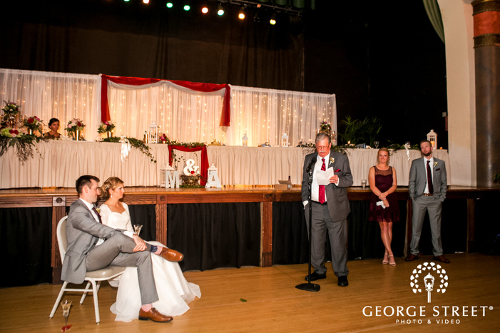 joyful bride and groom at reception toast at fountain square theatre in indianapolis