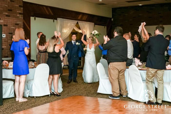 cheery bride and groom reception entrance wedding photo