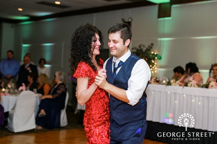 joyous groom and mother on dance floor wedding photo