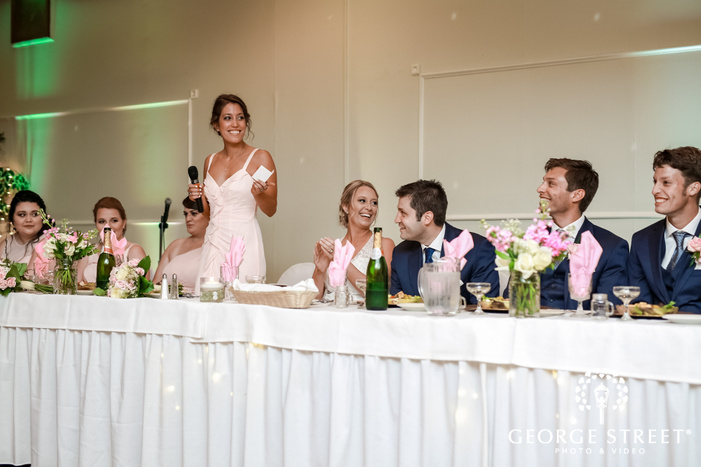 sweet bride and groom during guests speech wedding photo