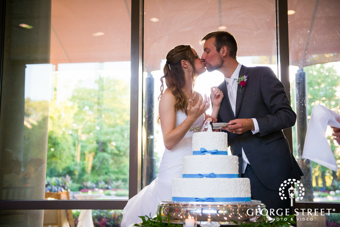bride and groom kiss with cake