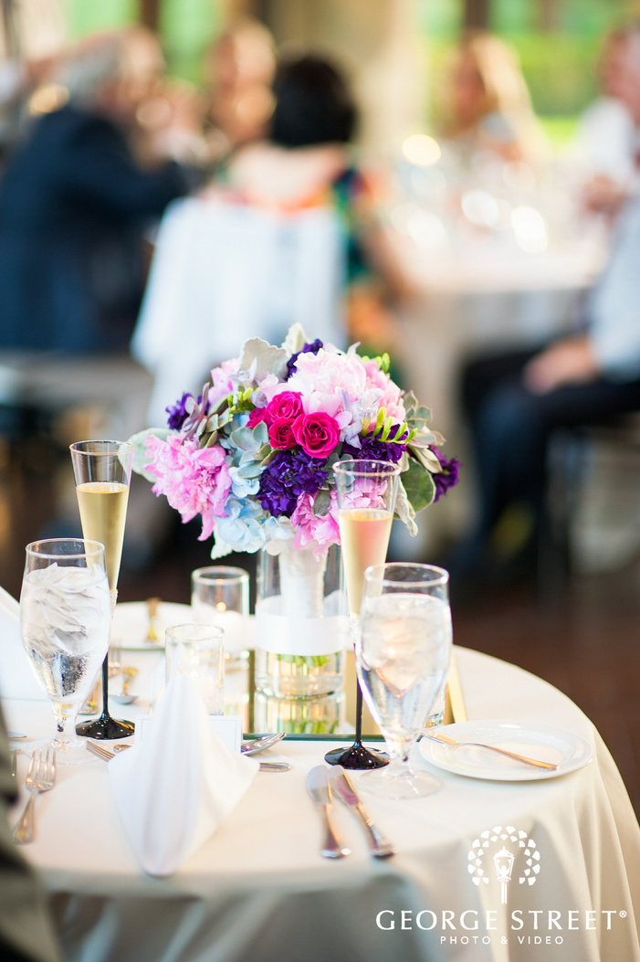 table with purple and pink wedding flowers
