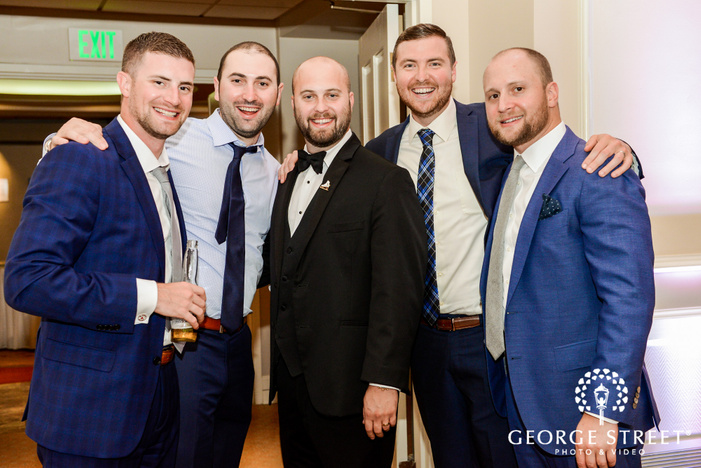 handsome groom and groomsmen in hall wedding photo