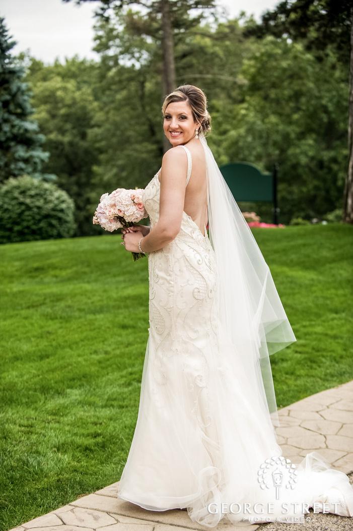 blissful bride in green garden near pine knob mansion wedding photography